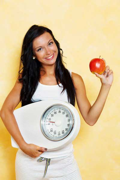 Young girl holding weighing machine and an apple