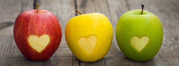Different color apple with carved heart sign
